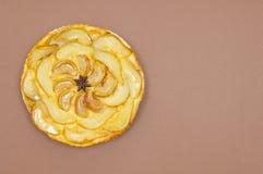 Весь пирог груши яблока Tatin tarte изолированный на коричневой предпосылке Стоковые Фотографии RF