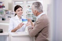 Весёлый женский аптекарь продавая лекарство стоковая фотография