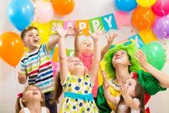 Весёлая группа детей при клоун празднуя день рождения Стоковое Изображение