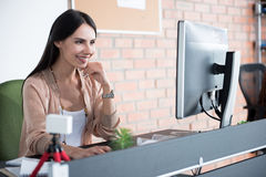 Весёлая усмехаясь женщина смотря вперед в офисе Стоковая Фотография