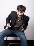 Весёлый бородатый человек в куртке и джинсах, сидя на стуле и держа оружие концепция гангстера Переговоры пошли не стоковое изображение rf
