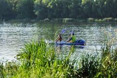 Весла rowing человека и женщины в каное на реке Стоковые Изображения RF