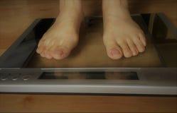 Вес женщины измеряя дома стоковое изображение