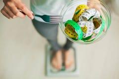 вес потери диетпитания Женщина держит шар и вилку с измеряя лентой стоковые фотографии rf
