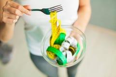вес потери диетпитания Женщина держит шар и вилку с измеряя лентой стоковое фото