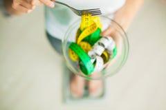 вес потери диетпитания Женщина держит шар и вилку с измеряя лентой стоковые фото