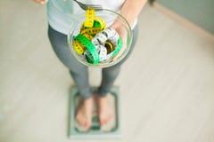 вес потери диетпитания Женщина держит шар и вилку с измеряя лентой стоковая фотография