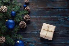 Ветви дерева, конусы сосны украшений рождества и рождества, голубые игрушки рождества на деревянной предпосылке основная упаковка Стоковые Изображения