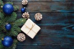 Ветви дерева, конусы сосны украшений рождества и рождества, голубые игрушки рождества на деревянной предпосылке основная упаковка Стоковое Изображение RF