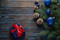 Ветви дерева, конусы сосны украшений рождества и рождества, голубые игрушки рождества на деревянной предпосылке основная упаковка Стоковое Изображение