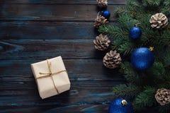 Ветви дерева, конусы сосны украшений рождества и рождества, голубые игрушки рождества на деревянной предпосылке основная упаковка Стоковые Фотографии RF