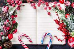 Ветви ели рождества, украшения, тросточки конфеты, который замерли красные ягоды, рамка конуса на тетради, космосе экземпляра для Стоковые Фото
