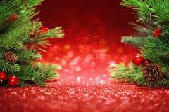 Ветви рождественской елки на блестящей красной предпосылке Стоковое Изображение RF