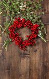 Ветви рождественской елки и красный венок на деревянном Стоковая Фотография RF