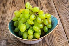 Ветвь зеленых виноградин на деревянной предпосылке Стоковое Изображение RF