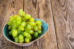 Ветвь зеленых виноградин на деревянной предпосылке Стоковые Фото