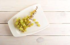 Ветвь зеленых виноградин на плите на белой деревянной предпосылке Стоковые Изображения