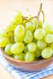 Ветвь зеленых свежих виноградин в деревянном шаре Стоковая Фотография