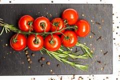 Ветвь зрелых томатов вишни, свежее розмариновое масло, allspice, фотография еды Стоковое Изображение RF