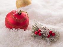 Ветвь рождественской елки, красные ягоды и красный шарик на снеге Стоковое Фото