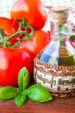 Ветвь свежего томата и бутылки оливкового масла с базиликом Стоковые Изображения