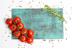 Ветвь томатов вишни зрелых, розмариновое масло, allspice, деревянная доска Стоковые Изображения RF