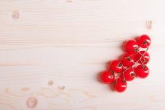 Ветвь томатов вишни на светлом взгляд сверху деревянного стола на th Стоковые Изображения RF