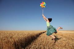 ветер пшеницы турбины девушки поля скача Стоковые Изображения