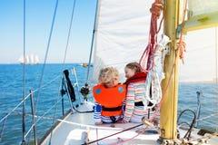 Ветрило детей на яхте в море Плавание ребенка на шлюпке стоковое фото
