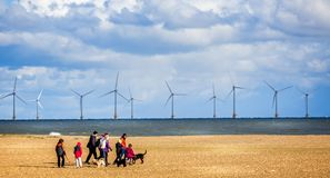 Ветровая электростанция с побережья Ярмут с собаками семьи идя на пляже в Great Yarmouth, Норфолке, Великобритании стоковые фотографии rf
