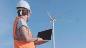 Ветротурбины вращаются пока техник работает ноутбук Чистая, дружественная к эко концепция энергии Мужчина сток-видео