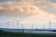 Ветротурбины в ландшафте с облаками и полях с немногим Стоковое Фото
