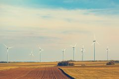 Ветротурбины в поле с голубым небом с облаками тонизировано Стоковое Изображение