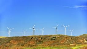 Ветротурбины на зеленом холме перед голубым небом Стоковые Фотографии RF