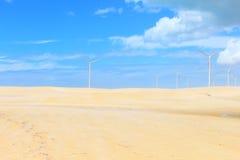 Ветротурбины на песчанных дюнах с голубым небом и облаками, Galinhos - RN, Бразилией Стоковая Фотография