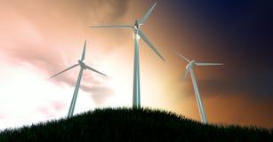 Ветротурбины на травянистом холме на зоре Стоковые Фотографии RF