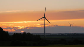 Ветротурбины обрабатывают землю с лучами света на заходе солнца стоковая фотография rf