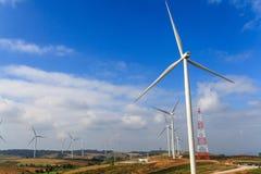 Ветротурбины производят электричество в горах и голубом небе стоковая фотография