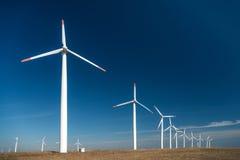 Ветротурбины против голубого неба производя электричество Стоковая Фотография
