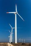 Ветротурбины против голубого неба производя электричество Стоковые Изображения