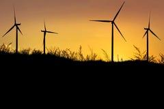 ветротурбины силуэта производя электричество на заходе солнца стоковые изображения