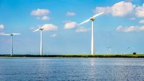 Ветротурбины, современные ветрянки, в ветровой электростанции вдоль берега Veluwemeer Стоковые Фото