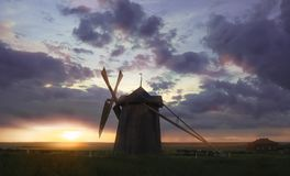 Ветрянка на восходе солнца в Нидерландах Красивая старая голландская ветрянка, зеленая трава, загородка против красочного неба с  Стоковое Изображение