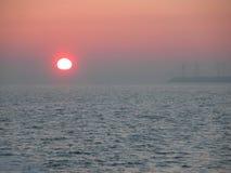 Ветрянки на море во время захода солнца Стоковые Фото
