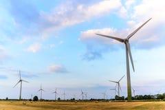 Ветрянки на полях, солнечный но облачном небе Стоковое Фото