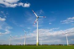 Ветрянки стоят на поле и производят зеленое электричество стоковое изображение