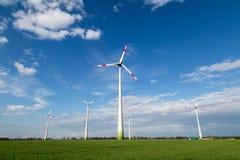 Ветрянки стоят на поле и производят зеленое электричество стоковая фотография