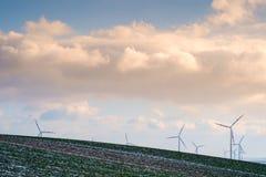 Ветр-парк в ландшафте с облаками и поле с меньшим снегом стоковое изображение