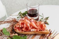 Ветчина в специях, тонко отрезанных на белой таблице с хлебом и античным столовым прибором стоковое изображение rf