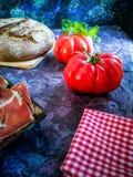 Ветчина, томат, хлеб и травы в составе на темной предпосылке стоковая фотография rf